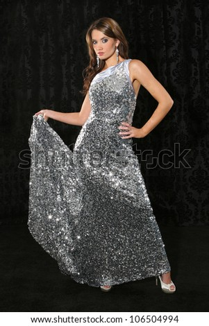 Beautiful young woman with long dark hair wearing a silver dress