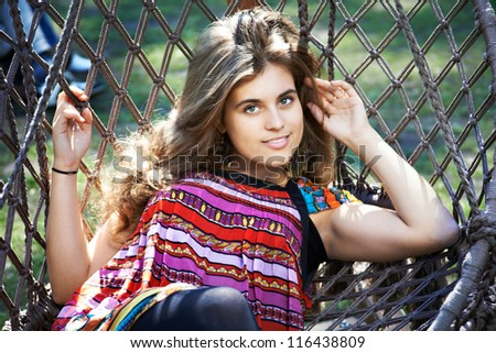 Beautiful young woman with long hair in a hammock in park