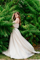beautiful young woman with long hair in a white dress posing in against the background of green leaves. Wedding walk. Bride. natural makeup.