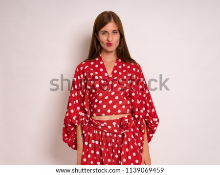Stock Photo beautiful young woman with long hair in red skirt and top in modeling photoshoot captured in photo studio against light backdrop