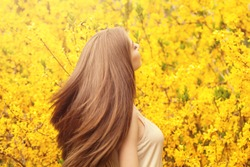 Beautiful young woman with long healthy hair against yellow flowers background. Girl with blowing hairstyle portrait
