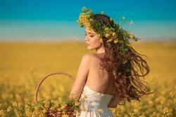 Beautiful young woman with long healthy hair over Yellow rape field landscape background. Attracive brunette girl with blowing hairstyle holding basket with flowers, outdoor portrait. Natural beauty.