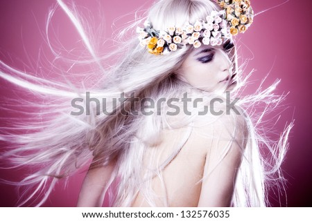beautiful young woman with long shiny blond flying hair and wreath of flowers