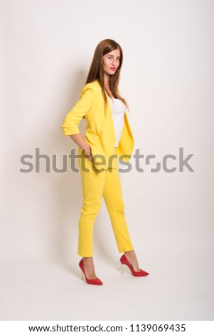 beautiful young woman with long straight hair in yellow suit in modeling photoshoot captured in photo studio against light backdrop