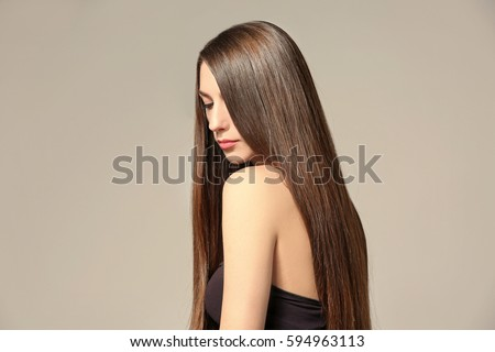 Beautiful young woman with long straight hair on light background #594963113
