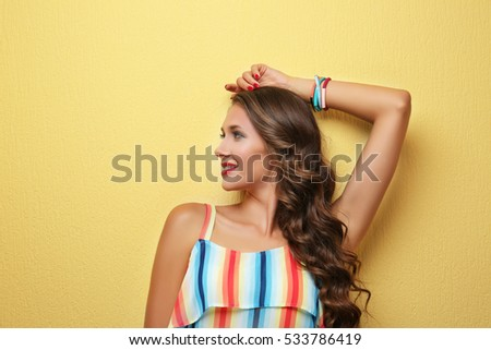 Beautiful young woman with make up and long  wavy hair on color background