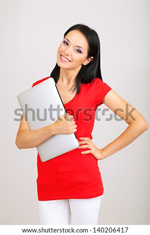 Beautiful young woman with notebook in room