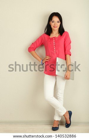Beautiful young woman with notebook in room - stock photo