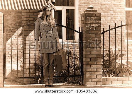 Beautiful young woman with old suitcase walking down the street.