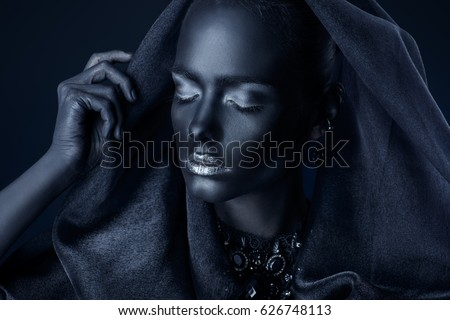 Beautiful young woman with perfect black skin and silver glitter lips wearing beautiful necklace and black veil. Cosmetics and make-up. Jewelry and bijouterie. Body painting project. African style.