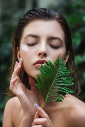 Beautiful young woman with perfect skin and natural make up posing front of plant tropical green leaves background with fern. Young model with wet hair care of her face and body.