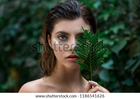 Beautiful young woman with perfect skin and natural make up posing front of plant tropical green leaves background with fern. Teen model with wet hair care of her face and body. SPA, wellness