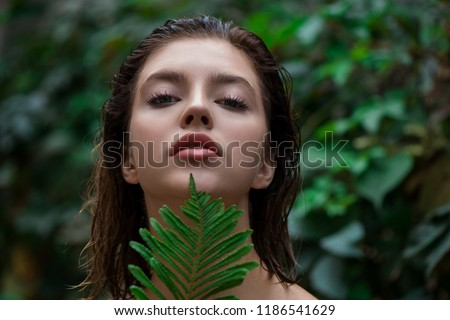 Beautiful young woman with perfect skin and natural make up posing front of plant tropical green leaves background with fern. SPA, wellness, bodycare and skincare.  Close up, selective focus. #1186541629