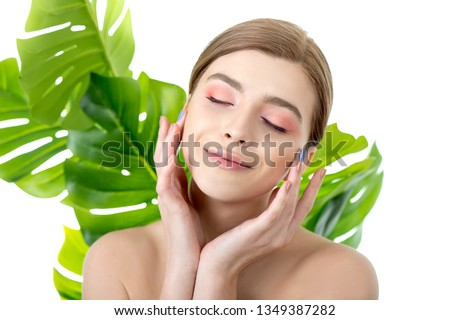 Beautiful young woman with perfect skin and natural make up posing front of plant tropical green leaves background. Teen model are of her face and body. SPA, wellness, bodycare and skincare. #1349387282