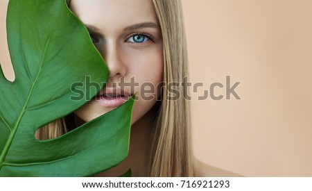 Beautiful young woman with perfect skin and natural make up. Teen model with green leaves. SPA,  skincare and wellness. Close up, selective focus. #716921293