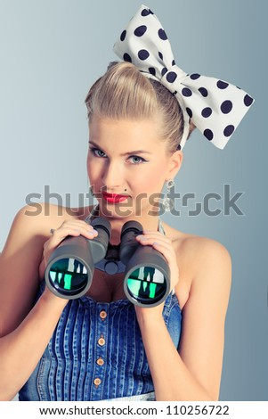 Beautiful young woman with pin-up make-up and hairstyle looking through binoculars.
