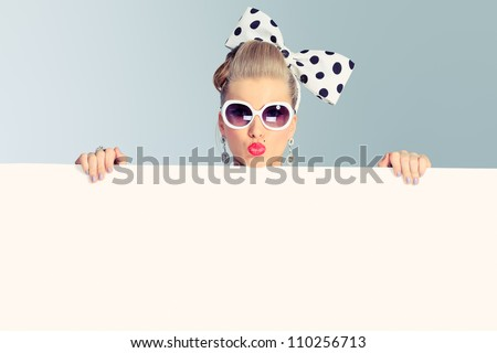 Beautiful young woman with pin-up make-up and hairstyle posing in studio with white board.