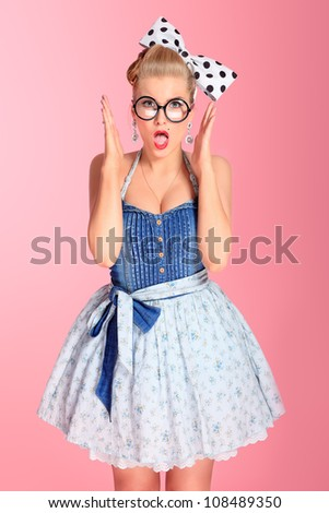 Beautiful young woman with pin-up make-up and hairstyle posing over pink background.