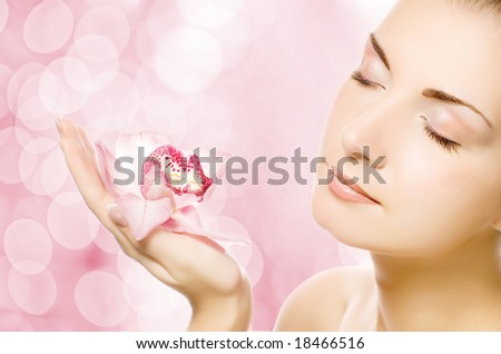 Beautiful young woman with pink orchid over abstract blurred background