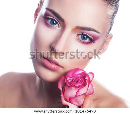 Beautiful young woman with pink rose bud - close up beauty portrait
