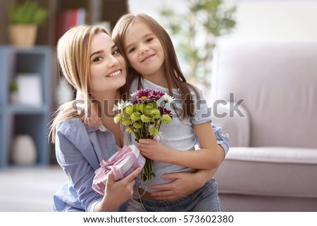 Beautiful young woman with present and bouquet of flowers from her daughter. Mother's day concept