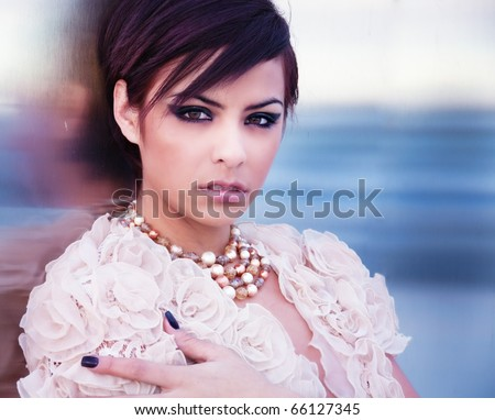 Beautiful young woman with pretty eyes and short hair wearing designer top and jewelery.