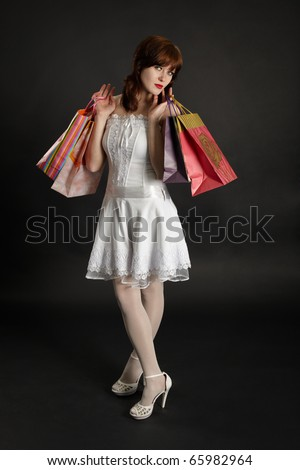 Beautiful young woman with purchases on a dark background