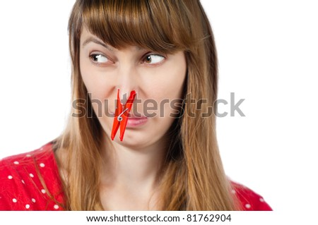 Beautiful young woman with red clothespin on her nose. Isolated on white background - stock photo