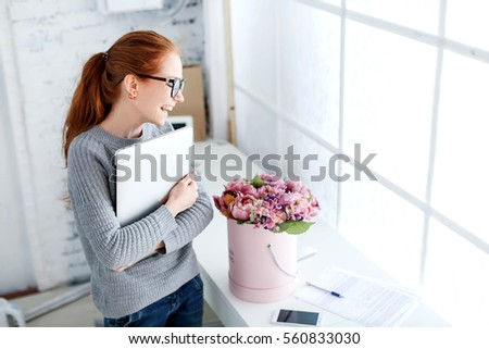 Beautiful young woman with red hair, an office worker at the workplace with a bouquet of flowers #560833030