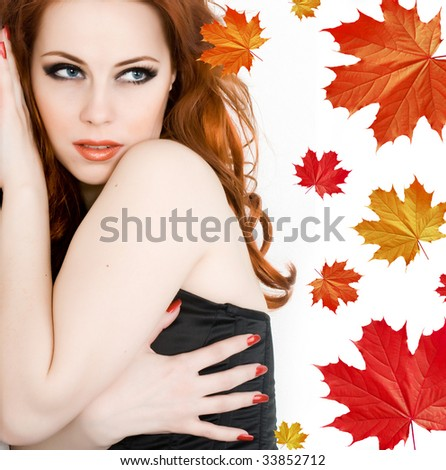 Beautiful young woman with red hair and maple leaves