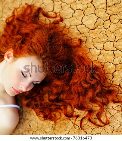 Beautiful young woman with red hair on the dried up ground.
