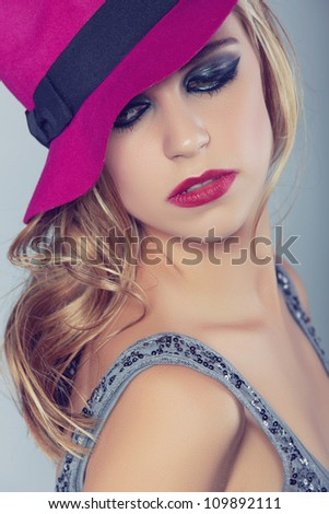 beautiful young woman with red lips and dark smoky eyeshadow wearing bright neon felt hat on studio background