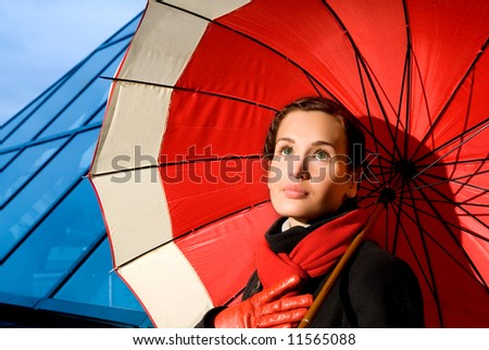 Beautiful young woman with red umbrella on rainy day