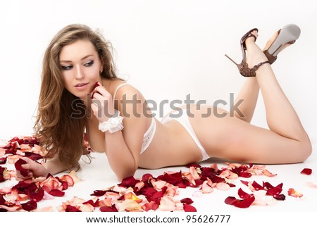 Beautiful young woman with roses petals.