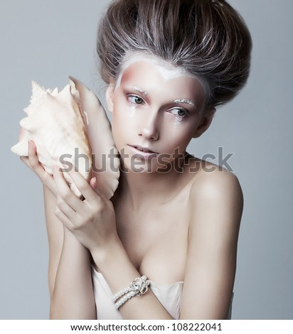 Beautiful young woman with seashell posing isolated. Series of photos
