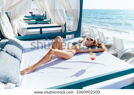 Beautiful young woman with sexy body in sunglasses and swimsuit, takes a sunbath while relaxing on a luxury sunbed, near the ocean. #1060902500