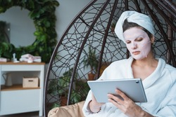 Beautiful young woman with sheet moisturizing face mask,tablet.Hanging wood swing chair.Bathrobe,towel in bedroom at home.Remote work.Self care,anti age treatment for skin.Web surfing,Online shopping.