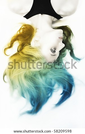 beautiful young woman with shiny silver makeup and tumbled colorful hair on white background