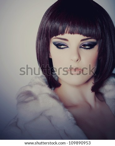 beautiful young woman with short brown hair in white fur coat wearing smoky purple eyeshadow and dramatic eyeliner.