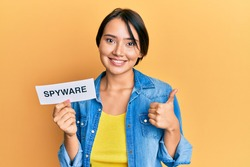 Beautiful young woman with short hair holding spyware text smiling happy and positive, thumb up doing excellent and approval sign