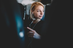 Beautiful young woman with short haircut listening favorite audio songs in modern earphones resting during flight and enjoying comfort first class sitting in seat on airplane board