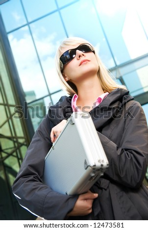 Beautiful young woman with silver case near the modern office building