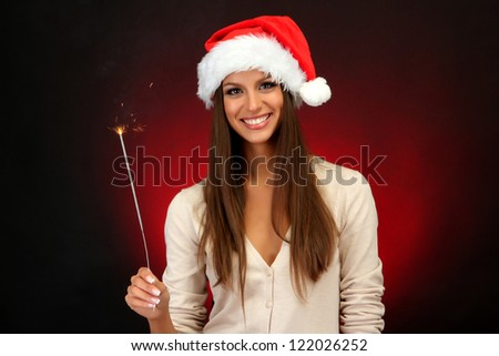 beautiful young woman with sparkler, on red background