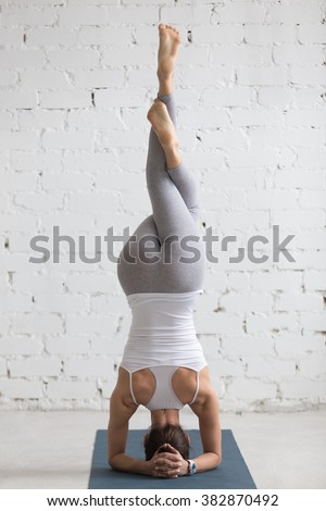 Beautiful young woman with sports smart watch working out indoors, doing yoga exercise on blue mat, variation of supported headstand, garuda salamba sirsasana with crossed legs, back view, full length