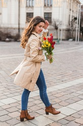 Beautiful young woman with spring tulips flowers bouquet at city street. Happy girl walking outdoors. Spring portrait of pretty female in old town