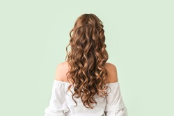 Beautiful young woman with stylish hairdo on color background, back view