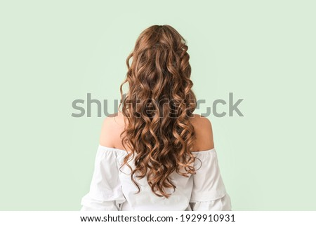 Beautiful young woman with stylish hairdo on color background, back view Foto stock ©