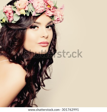 Beautiful Young Woman with Summer Pink Flowers. Long Permed Curly Hair and Fashion Makeup. Beauty Girl with Flowers Hairstyle.