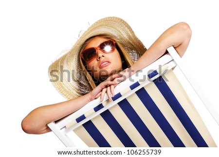 Beautiful young woman with sunglasses relaxing on beach chair isolated on white background