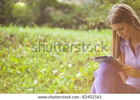 Beautiful Young Woman With Tablet Computer In Park